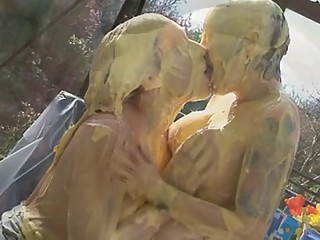 Sexy naked girls kiss passionately under a steady stream of custard